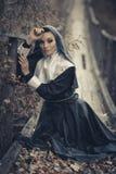Seductive,sexual nun sits on the wooden bridge outdoors and pray for.Sexual nun with creative make-up. Very creative shooting.Beautiful nun,sexy nun,young nun Stock Image