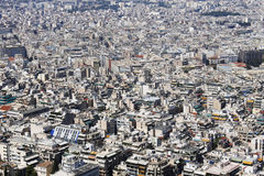 Very crowded city with a lot of buildings. View over a dense residential area from Athens Greece. These white buildings have many nice terraces and rooftop Stock Photos