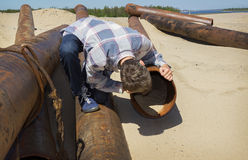 Very curious young man looks into  pipe Stock Photo