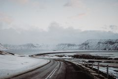 A curvy road in Iceland. A very curvy road leading towards a bridge over a lake in Iceland stock image