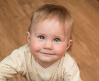 Very cute baby smiles looking up at the camera Stock Image