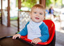 Very cute beautiful baby boy sitting in the highchair black Royalty Free Stock Image