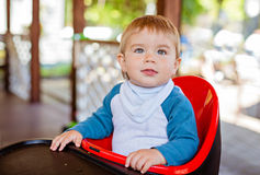 Very cute beautiful baby boy sitting in the highchair black Royalty Free Stock Photography