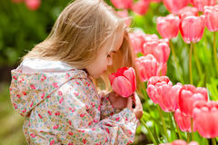 Very cute beautiful girl blonde in pink coat costs around flower Royalty Free Stock Photography