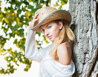 Very cute blond woman sitting down outdoor with a hat near a tree Stock Photo