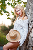 Very cute blond woman sitting down outdoor with a hat near a tree Stock Photography