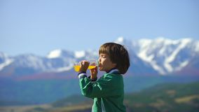 A very cute boy drinks orange juice on a background of beautiful mountains. 4k Little boy relaxes on the top of the hill