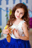 Very cute curly haired young girl in a blue skirt, close up stock photography