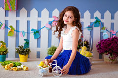Very cute curly haired young girl in a blue skirt sitting on the Royalty Free Stock Photography