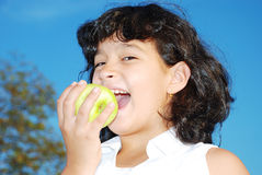 Very cute girl eating an apple in outdoor scene Royalty Free Stock Images