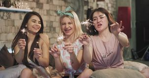 A very cute ladies multi ethnic enjoy the time together at home in bedroom with pajamas playing with a sparkling. Fireworks and have a fun stock video