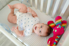 Very cute little baby boy lying on the bed at the back in the cr Royalty Free Stock Images