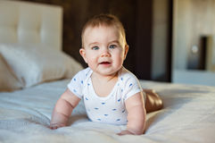 Very cute little baby boy lying on the bed on his tummy on a lig Royalty Free Stock Photos