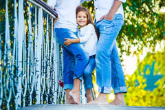Very cute little blonde girl holding the foot mom Stock Images