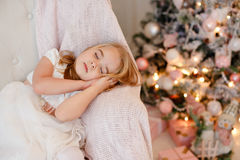 Very cute little girl blonde in white dress sitting on a chair a Stock Image