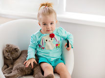 Very cute little girl in the blue jacket sits on the chair with Royalty Free Stock Images