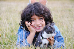 Very cute little girl with cat. On meadow Stock Photos