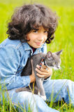 Very cute little girl with cat on meadow. Is happy Royalty Free Stock Photos