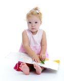 Very cute little girl reading a book sitting on Stock Photos