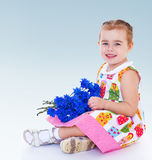 Very cute little girl sitting on the floor Stock Images