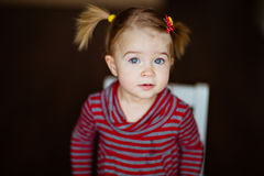 Very cute little girl in a striped dress sitting on a chair Stock Images