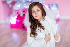 Very cute long-haired young girl with blue eyes in a white coat Stock Image