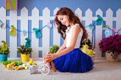 Very cute long-haired young girl in a blue skirt sitting on the Royalty Free Stock Photo