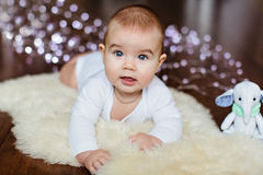 Very cute smiling baby lying on the floor on the background of C Royalty Free Stock Photography