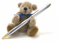 Very cute teddy bear holding a pen Royalty Free Stock Photos
