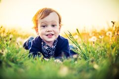 Very cute toddler smiling portrait in white dandelion meadow