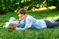 Very cute, young boy in round glasses and blue shirt reads book lying on the grass next to backpack and globe. Education,. Back to school concept stock photos