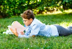 Very cute, young boy in round glasses and blue shirt reads book lying on the grass next to backpack and globe. Education,. Back to school concept stock images