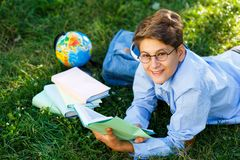 Very cute, young boy in round glasses and blue shirt reads book lying on the grass next to backpack and globe. Education. Back to school concept royalty free stock photo