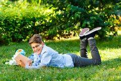 Very cute, young boy in round glasses and blue shirt reads book lying on the grass next to backpack and globe. Education. Back to school concept royalty free stock image
