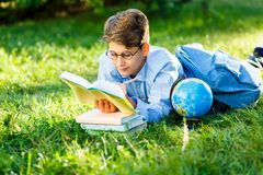 Very cute, young boy in round glasses and blue shirt reads book lying on the grass next to backpack and globe. Education,. Back to school concept royalty free stock photo