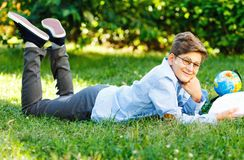 Very cute, young boy in round glasses and blue shirt reads book lying on the grass next to backpack and globe. Education. Back to school concept stock photo