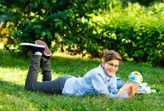 Very cute, young boy in round glasses and blue shirt reads book lying on the grass next to backpack and globe. Education. Back to school concept stock image