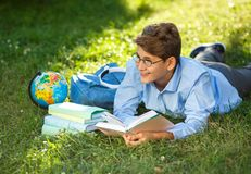 Very cute, young boy in round glasses and blue shirt reads book lying on the grass next to backpack and globe. Education. Back to school concept stock images