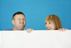 Very Cute Young Couple Behind White Cover Stock Image