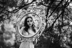 Black and white art monochrome photography. Very cute young girl with the frame of the mirror. Doll appearance Royalty Free Stock Image