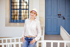 Very cute young girl in a hat, jeans and white shirt standing on. A background of blue door and smiles Royalty Free Stock Photography