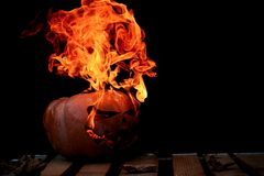 A very dangerous dangerous Halloween pumpkin, with a stern gaze. And a smirk of a villain, in the darkness on a wooden pallet, spouts out the mouths and eyes of Royalty Free Stock Images