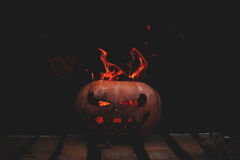 A very dangerous dangerous Halloween pumpkin, with a stern gaze. And a smirk of a villain, in the darkness on a wooden pallet, spouts out the mouths and eyes of Stock Image