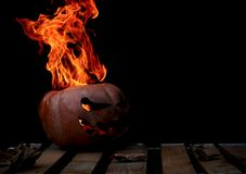 A very dangerous dangerous Halloween pumpkin, with a stern gaze. And a smirk of a villain, in the darkness on a wooden pallet, spouts out the mouths and eyes of Stock Photography