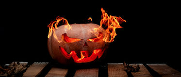 A very dangerous dangerous Halloween pumpkin, with a stern gaze. And a smirk of a villain, in the darkness on a wooden pallet, spouts out the mouths and eyes of Stock Photo
