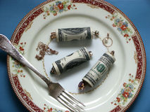 Very dear dish. Dish from money, a stuffing from jewelry on a plate with a plug Stock Image
