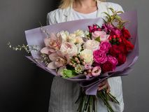 Very delicate handmade bouquet in the hands of the girl florist, a great gift, fresh and neat, interesting gradient royalty free stock photography