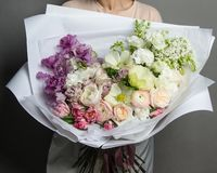 A girl is holding a beautiful bouquet of exclusive fresh flowers in a box. A great gift for women`s day stock images