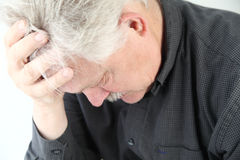 Very depressed older man. Senior man bent over with grief or depression Stock Image