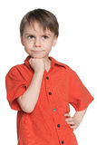 Very difficult task. A very thoughtful little boy in a red shirt on the white background Stock Image
